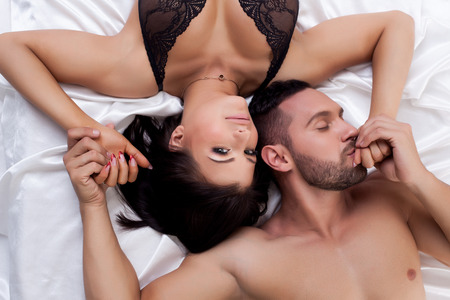 Top view of loving young couple laying in bed photo