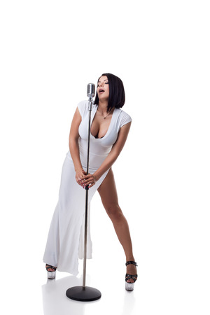 Gorgeous busty singer posing with microphone in studio Stock Photo