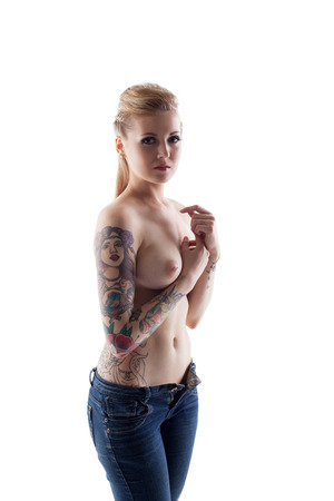 topless jeans: Studio shot of tattooed woman with pierced nipples, close-up
