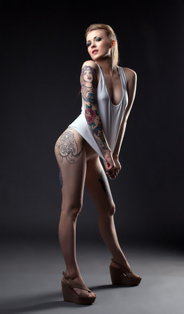 tattoo face: Sexy slim model with tattoos posing in gray T-shirt