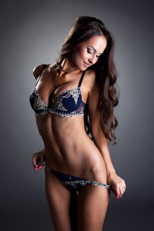 femme brune sexy: Sourire modèle plantureuse enlève sa culotte à la caméra