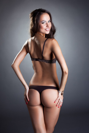 thong woman: Rear view of smiling slim woman posing in bra and thong
