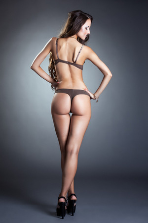 Rear view of high slender model in bra and thong