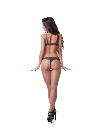 thong woman: Rear view of slender tanned model with elastic skin