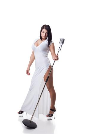 tetona: Morena joven atractiva en vestido largo posando con micrófono