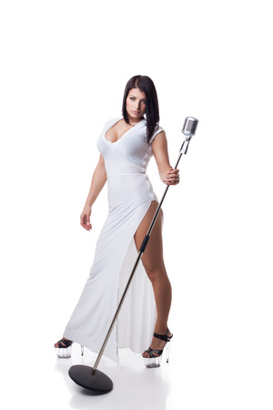 busty woman: Sexy young brunette in long dress posing with microphone