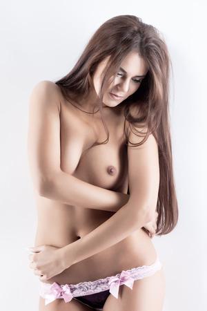 topless brunette: Seductive topless model posing in panties, on gray backdrop