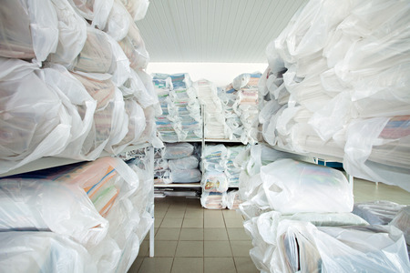dries: Image of shelves with clean clothes in dry cleaning Stock Photo