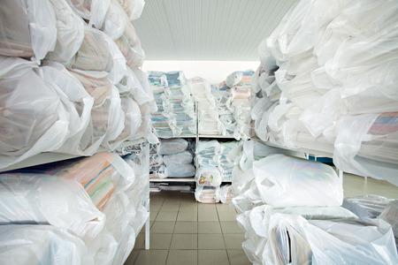 lavanderia: Imagen de estantes con ropa limpia en la limpieza en seco