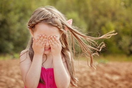 jolie petite fille: Drôle de petite fille jouant à cache-cache avec la caméra