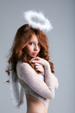 Portrait of lovely red-haired angel posing in studio Stock Photo