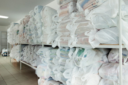 Image of racks with clean linen in laundry room photo