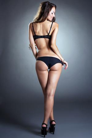 booty: Rear view of slim tanned underwear model posing in studio Stock Photo