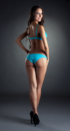 sexy ass: Smiling skinny model posing in blue lingerie, on gray backdrop
