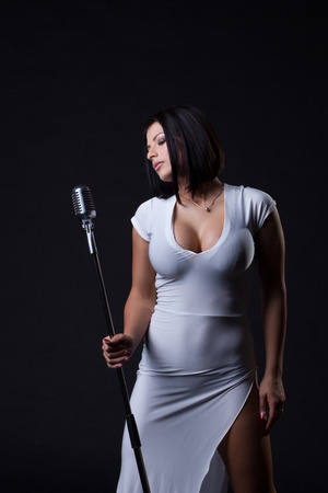 role model: Image of busty slim singer posing in studio, on gray backdrop