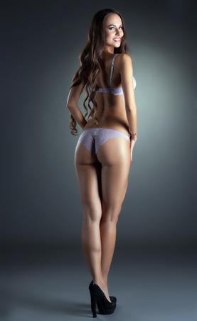 culo di donna: Affascinante giovane donna pubblicizza biancheria intima, su sfondo grigio