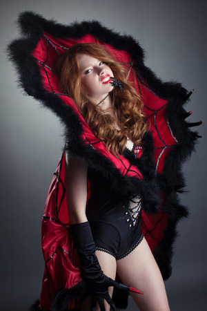 Hot redhead girl posing in fashionable spider costume