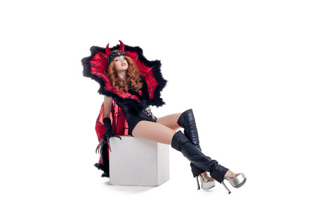 Young confident woman posing dressed as devil, isolated on white photo