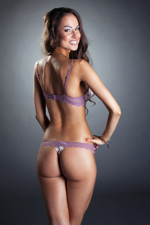 thong woman: Charming young woman in lingerie posing back to camera