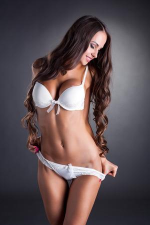jungen unterwäsche: Bild von sexy Dessous-Model Ausziehen in die Kamera, auf grauem Hintergrund