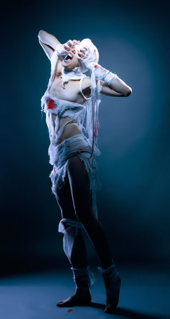 Image of screaming model posing as zombie, on blue backdrop photo