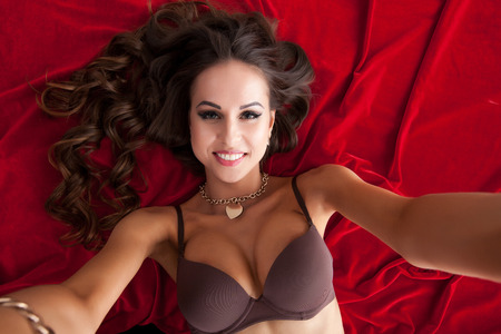 red bra: Beautiful busty model taking selfie while lying on red satin bedsheet