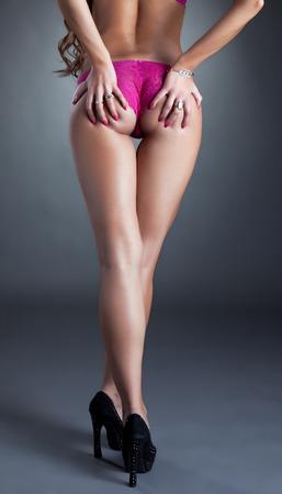 bragas: Estudio tirado de modelo de piernas largas posando en ropa interior de color fucsia Foto de archivo