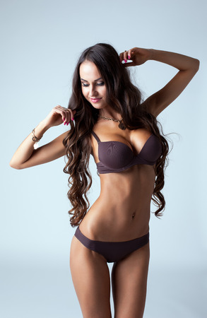 tanned girl: Portrait of beautiful tanned woman posing in lingerie