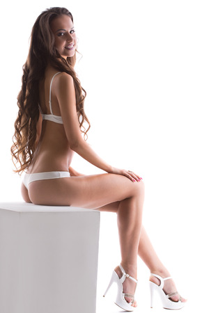 woman panties: Image of charming lingerie model posing sitting on cube Stock Photo