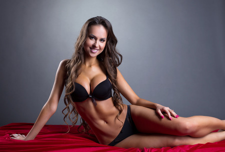 busty woman: Smiling athletic model posing in lingerie, on gray backdrop