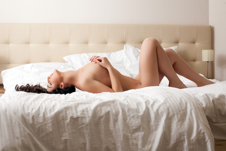 brunette naked: Image of sensual naked girl lying on bed in hotel room