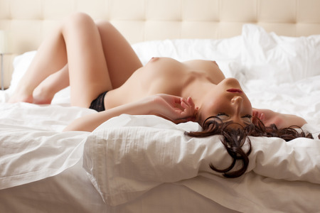 seins nus: Image de belle femme seins nus dans le lit de repos