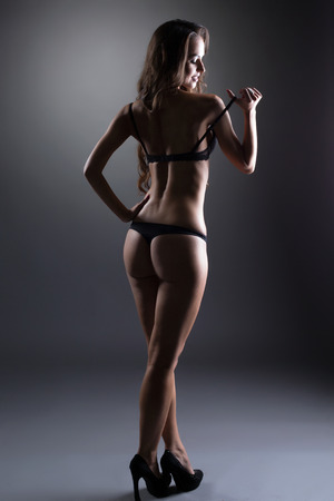 thong woman: Flirtatious underwear model posing back to camera, on gray backdrop Stock Photo