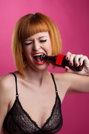 Portrait of cute redhead girl opens bottle by her mouth photo