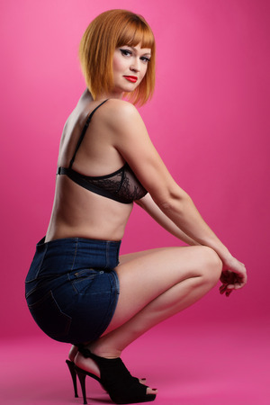 Slender red-haired model posing on pink background photo