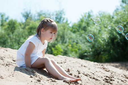 little model: Image of curious little model sitting on sand in park
