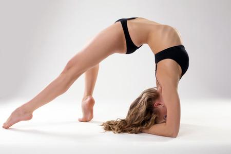 Image of flexible woman doing pilates exercises in studio Stock Photo