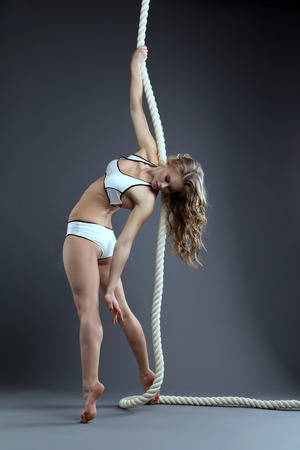 woman rope: Studio shot of sexy slim woman posing hanging on rope Stock Photo