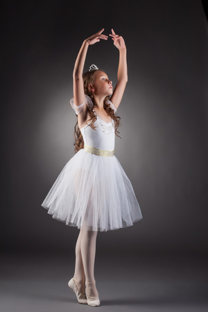 Graceful little ballerina posing on gray backdrop