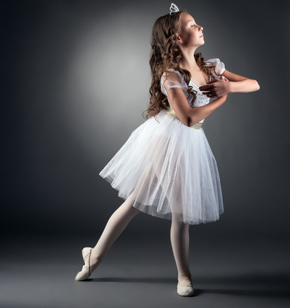 Side view of adorable little ballerina posing in studio Stock Photo