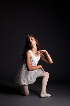 Image of smiling young ballerina posing on gray background