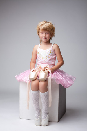 Nice little ballerina posing with pointes at camera