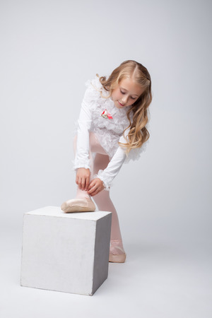 Curly little girl tying pointe in studio, on gray backdrop