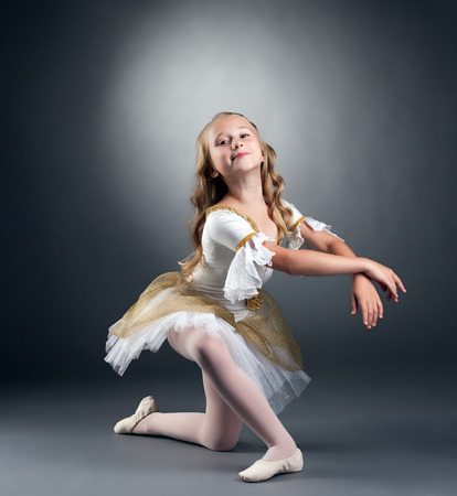 ballet child: Image of nice little ballerina posing at camera, on gray background