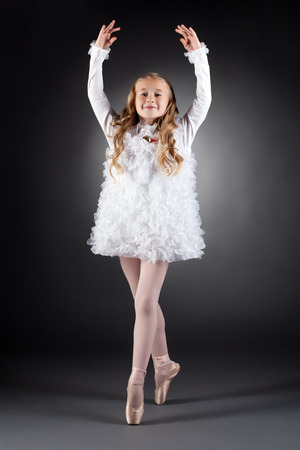 Smiling curly-haired girl dancing on pointes in studio
