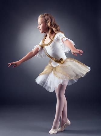 'ballet girl': Cute little ballerina dancing in studio, on gray backdrop Stock Photo