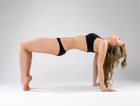 young girl barefoot: Flexible pilates trainer exercising in studio, on gray background Stock Photo