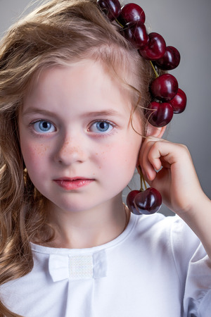tries: Image of adorable girl tries on cherries as earring, close-up Stock Photo