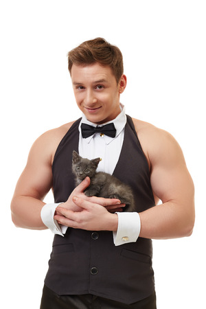 male costume: Handsome muscular male dancer posing with adorable kitten Stock Photo