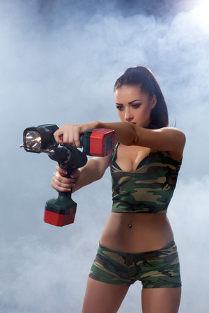 militaire sexy: Image of exciting brunette posing with flashlight and drill